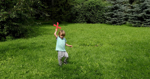 Little kid playing with red boomerang outdoors Archivo