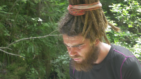 Hipster Male with Dreadlocks Looking for Paper Map in Forest Footage