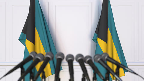 Bahamian official press conference. Flags of the Bahamas and microphones Live Action