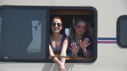 Young women looked out of the window of the trailer and dancing. The wind plays Live Action
