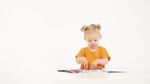 Little blonde baby girl coloring picture with two colorful crayons against white Live Action