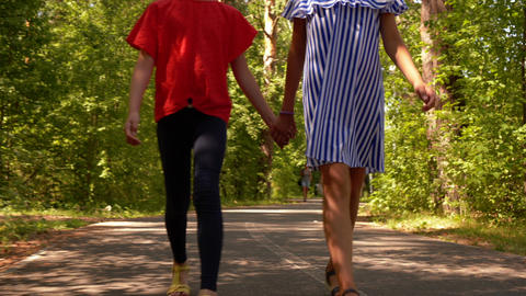 Two teens girls friend walking in park together holding hands, legs closeup Live Action