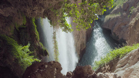 Idyllic Waterfall in cave, in rainforest landscape. Water flowing surrounded by Live Action