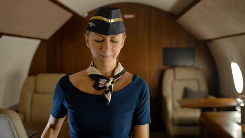 Cabin crew air hostess joyfully dancing inside of private jet cabin Live Action