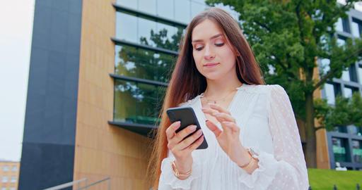 Lady Using a Phone Outdoors Acción en vivo