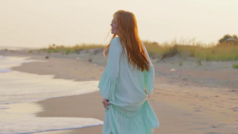Carefree woman dancing on the sunset on the sea beach. Girl spinning Live Action