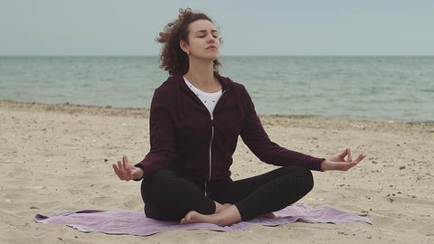 Beautiful and young woman practice yoga on the beach. Healthy lifestyle Footage