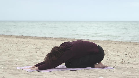 Beautiful and young woman practice yoga on the beach. Healthy lifestyle. Young woman doing Live Action