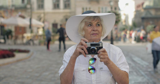 Senior female tourist exploring town and makes a photo with retro photo camera Live Action