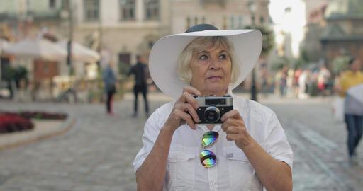 Senior female tourist exploring town and makes a photo with retro photo camera Footage