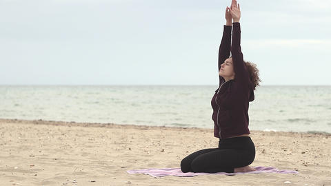 Beautiful and young woman practice yoga on the beach. Healthy lifestyle. Young woman doing Footage