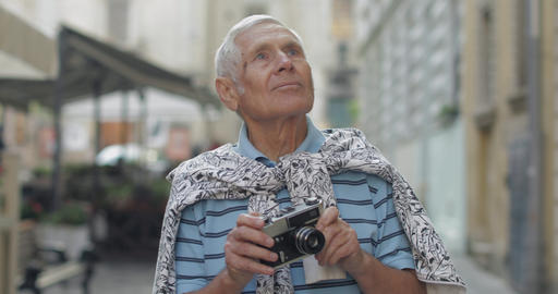 Senior male tourist exploring town and makes a photo with retro photo camera Footage