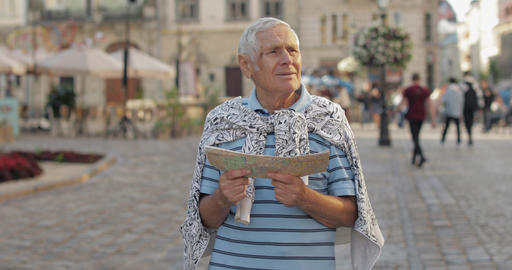 Senior male tourist exploring town with a map in hands. Looking for the route Footage