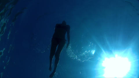 Young woman swimming in the blue and clear sea. Young woman swimming underwater Live Action