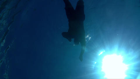 Young man swimming underwater in blue and clear sea Footage