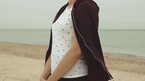 Young woman standing on the beach while wind is blowing. Young woman dress herself with sweatshirt Live Action