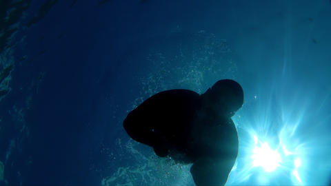 Young man dive into the blue sea and catch the camera with hand Footage