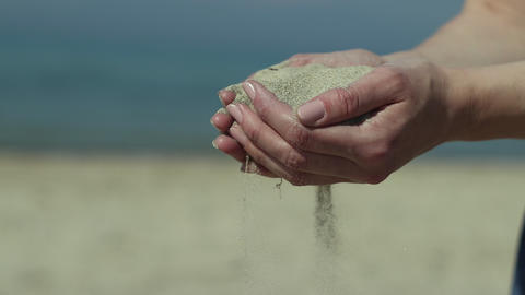 Young woman hold dry sand in hands on the beach and sand fall between fingers. Slow motion. Close up Live Action