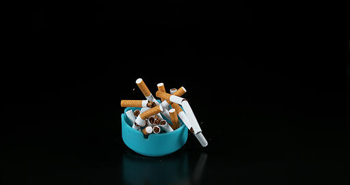 Ashtray and Cigarettes Falling against Black Background, Slow Motion 4K Live Action