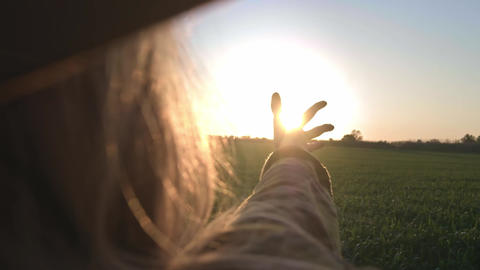 Girl looks at the sun through her hand. Woman playing hand with the rays of the Footage