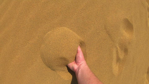 A man walks on the sand in the desert. He takes a handful of sand with his hand Live Action