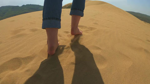 A woman runs along the sand in the desert. A girl runs barefoot on a sand dune Live Action
