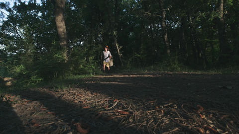 A young peasant walking in the woods. Hiker hiking in forest at sunset. Active Footage