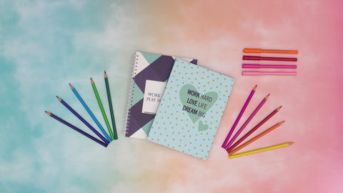 Stop motion animation of two notebooks and colored pencils appear on beautiful colored background. Animation