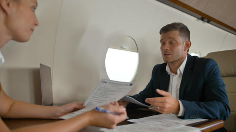 Two business people inside of luxury jet cabin sign documents Footage
