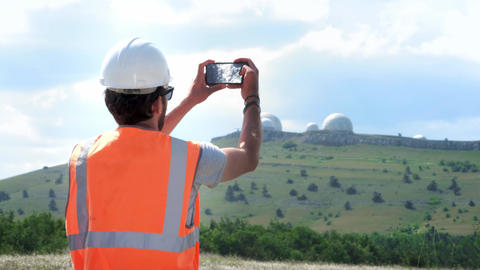 A male engineer or builder in a white helmet and vest makes a photograph of the Footage