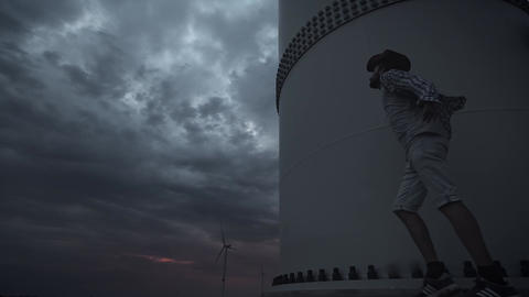 A young guy next to the Wind Turbines, produce ecological energy. The concept of Footage