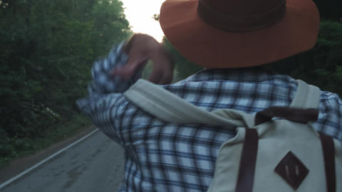 Traveler man picking up her backpack. Backpacker man lifts her bag from the road Footage