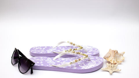 Purple slippers and sunglasses and sea shell on white background - Stop motion Animation