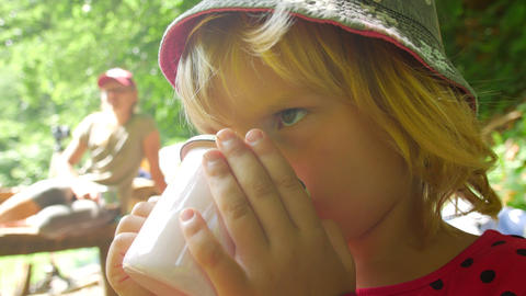 Child drinks tea from a mug. Rest on a hike on a hiking route Live Action
