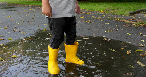 Baby stomping through puddles in yellow rubber boots Live Action