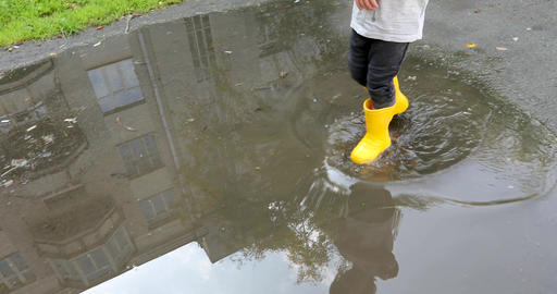 Baby stomping through puddles in yellow rubber boots Footage