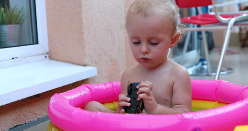 Adorable Baby Playing With Toys In A Mini Pool GIF