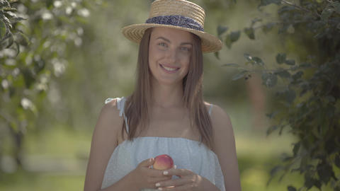 Attractive young positive woman in straw hat and white dress looking at the Footage