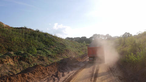 Heavy truck carrying sand on dusty dirt road Live Action