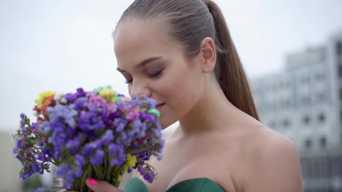 Portrait of a adorable girl in chic dress smelling a fragrant bouquet of Live Action