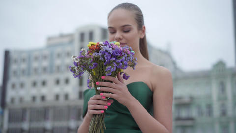 Beautiful girl in chic dress standing with fragrant bouquet of wildflowers on Live Action