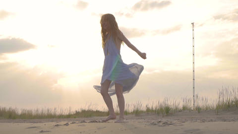 Carefree woman dancing on the sunset on the sea beach. Girl spinning. Femininity Live Action
