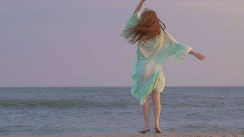 Carefree woman dancing on the sunset on the sea beach. Girl spinning Footage