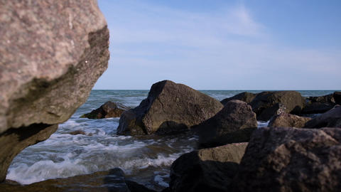 view of the sea surface due to large stones, camera moving forward Acción en vivo
