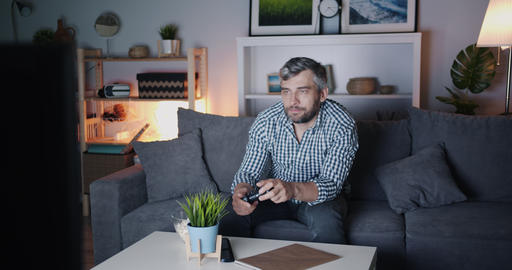 Man playing video game and chewing popcorn enjoying leisure at night Footage