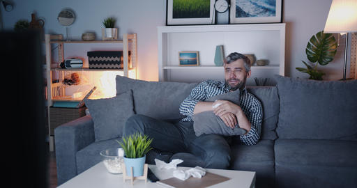 Sensitive man watching sad movie on TV at home wiping eyes with paper tissue Footage