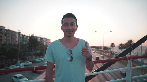 Attractive charismatic young guy thumbs up with beautiful sun light. Ok, good, perfect gesture Footage