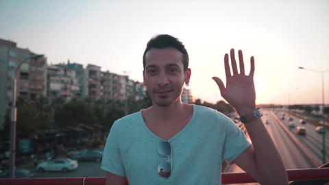 Young casual man is waving hands in urban, bridge in front of highway afternoon time with Footage
