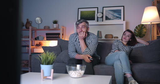 Girl and guy watching TV at night with sad faces, guy wiping eyes with tissue Footage