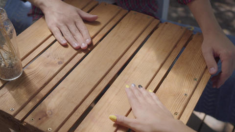 Close-up of male and female hands at the table outdoors. Man and woman having Footage